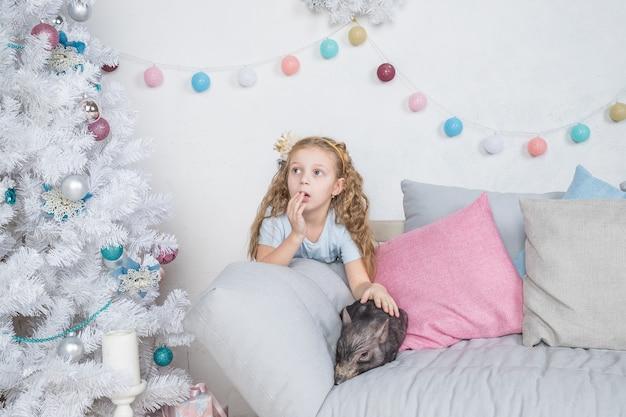 Cerdo como símbolo de suerte y calendario chino de año nuevo 2019. la chica divertida está sorprendida por el mini cerdo del bebé en el sofá cerca del árbol de navidad con regalos, que simboliza el año nuevo 2019