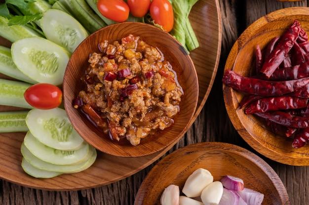 Cerdo dulce en un tazón de madera con pepino, frijoles largos, tomates y guarniciones.
