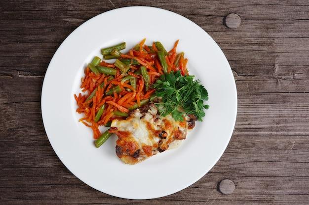 Cerdo frito picado con queso, judías verdes y zanahoria. vista superior.
