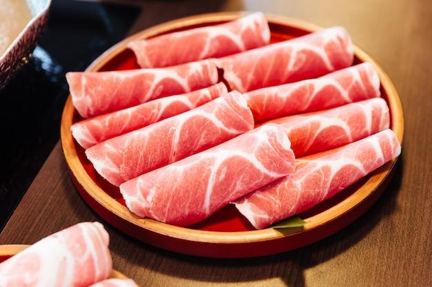 Cerdo kurobuta (cerdo negro) premium rare slices con textura de alto mármol en un círculo de madera.