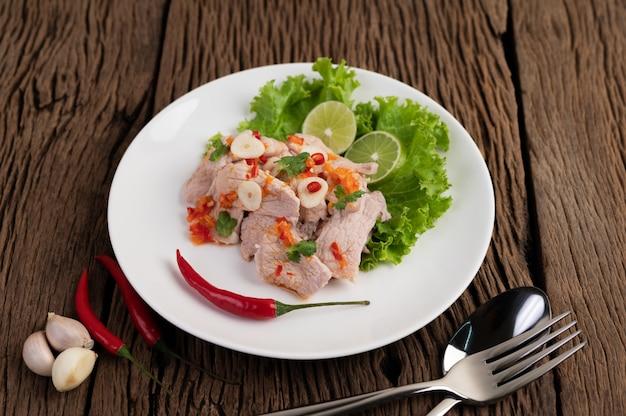 Cerdo picante con ensalada, galangal, chile, tomate y ajo en un plato blanco sobre un piso de madera.