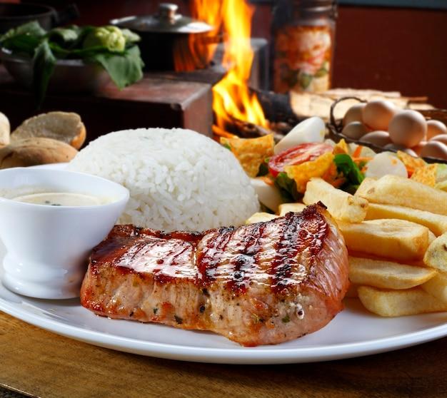 Cerdo a la plancha con patatas fritas y verduras