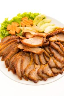 Cerdo rojo asado a la barbacoa con salsa dulce al estilo de comida china en plato blanco