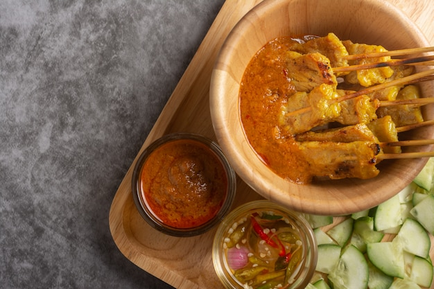 Cerdo satay en receta tailandesa del cuenco de madera.
