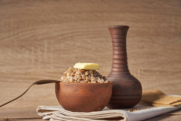 Cereal de alforfón cocido en un recipiente de arcilla marrón en la mesa de madera. grano sin gluten para una dieta saludable