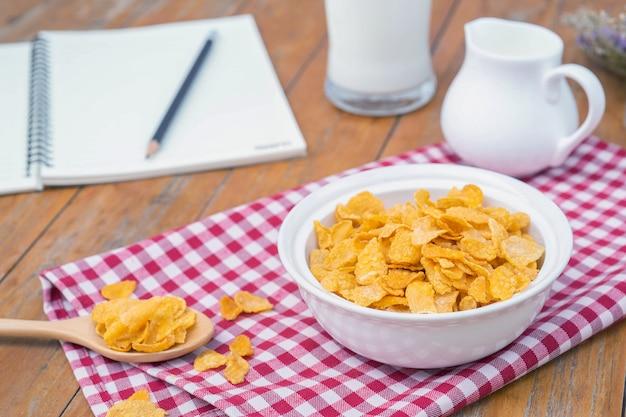 Cereal de los copos de maíz en un tazón de fuente blanco con una cuchara. desayuno de la mañana.