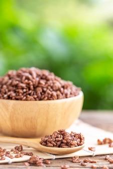 Cereal de desayuno, arroz inflado con cacao en un tazón en mesa de madera con espacio verde borroso