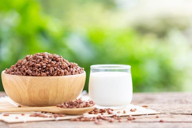 Cereal de desayuno, arroz inflado con cacao en un tazón y vaso de leche en la mesa de madera