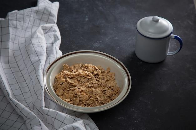 Cereal de desayuno de salvado de trigo sin leche en un tazón. fondo negro con servilleta casera.