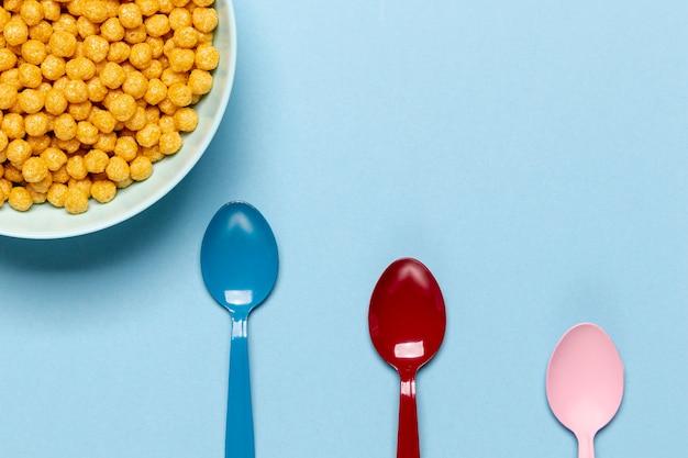 Cereal dorado en un tazón azul con vista superior de la cuchara