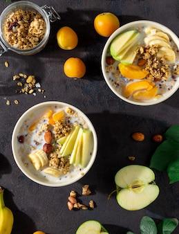 Cereal de granola con frutas, nueces, leche y mantequilla de maní en un tazón sobre un fondo blanco. vista superior de cereales para el desayuno saludable