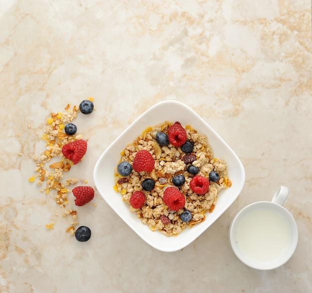 Cereal de muesli con frambuesas y arándanos y taza de leche