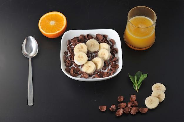 Cereales de chocolate con plátanos y jugo de naranja.