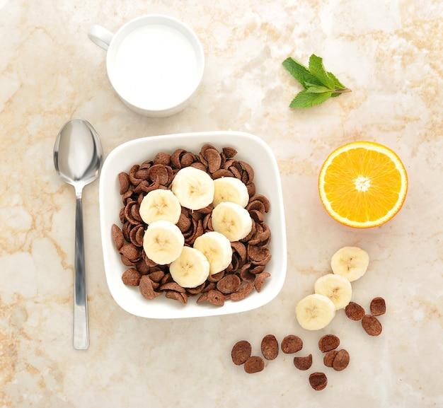 Cereales de chocolate con plátanos y naranja y leche.