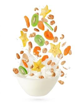 Cereales copos de maíz con frutas y nueces cayendo en el recipiente con salpicaduras de leche