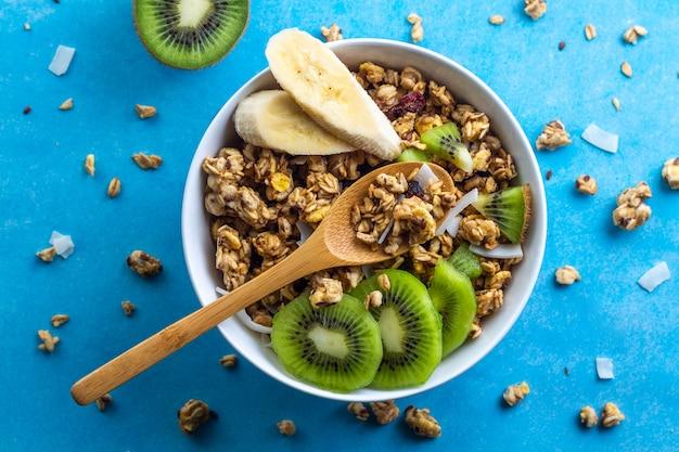 Cereales de desayuno secos. crujiente de miel muesli tazón con rodajas de plátano fresco y kiwi sobre un fondo azul. comida sana, saludable y con fibra. vista superior. hora del desayuno