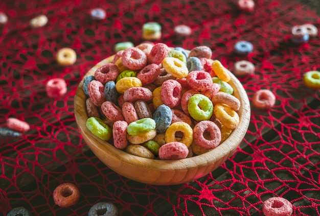 Cereales de frutas redondos coloridos en un cuenco de madera sobre una mesa roja, con algunos esparcidos fuera del cuenco.