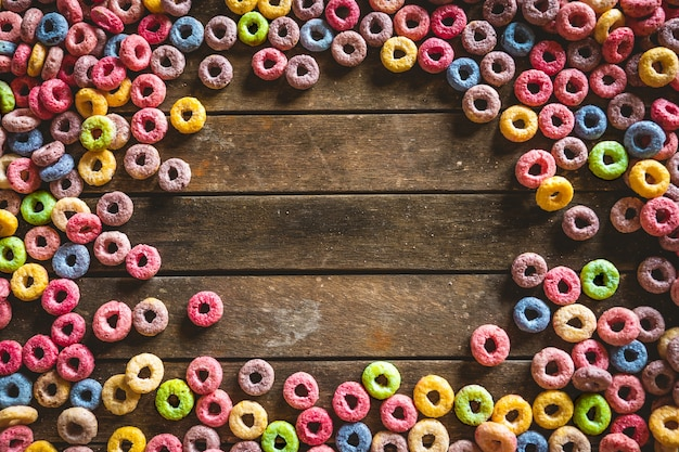 Cereales de frutas redondos coloridos esparcidos sobre una mesa de madera marrón con espacio en el medio.
