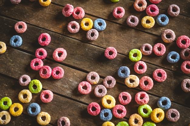 Cereales de frutas redondos coloridos esparcidos sobre la mesa de madera marrón.