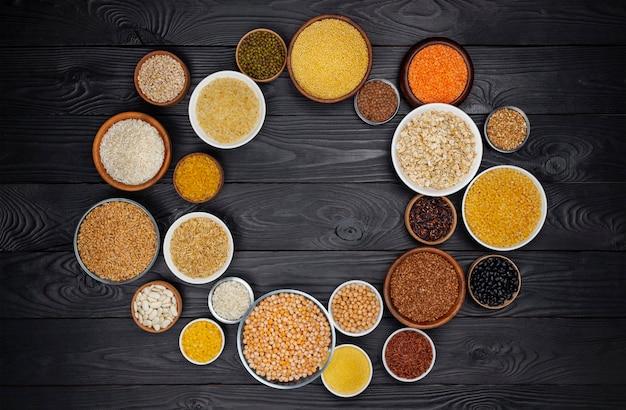 Cereales, granos, semillas y granos fondo negro de madera