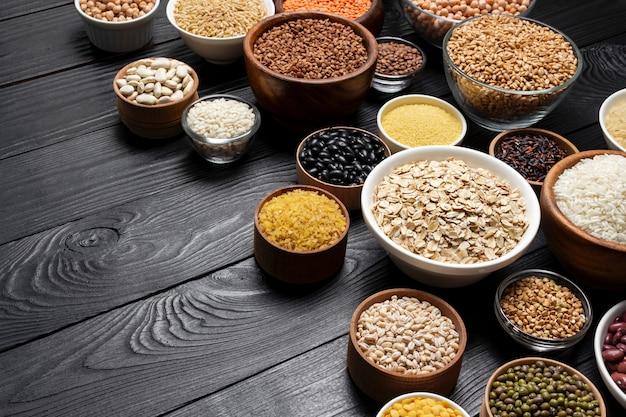 Cereales, granos, semillas y granos en la superficie de madera negra.