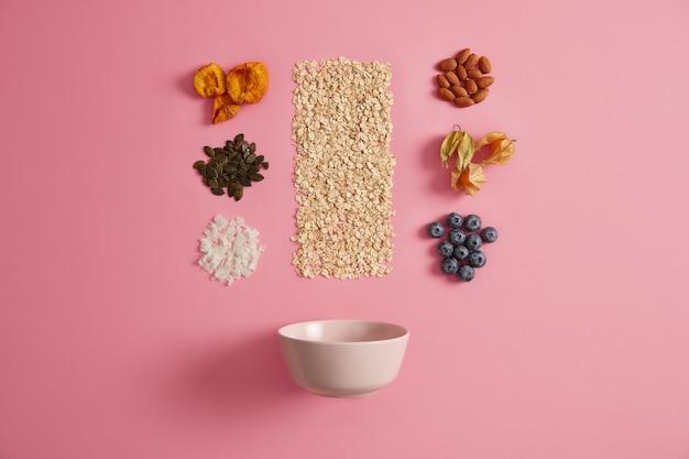 Cereales con manzanas secas, dátiles, anacardos, pistachos alrededor de botella con leche
