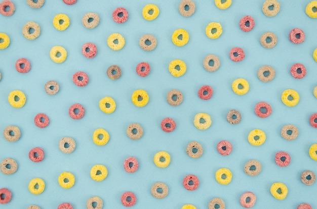 Cereales multicolores con sabor a fruta sobre fondo azul.