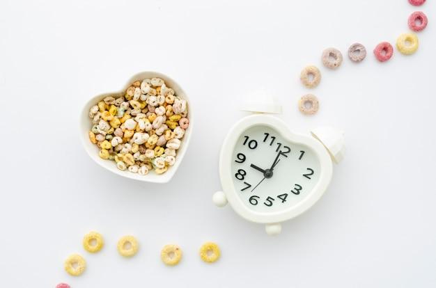 Cereales y reloj sobre fondo blanco.