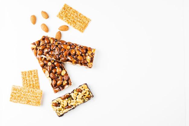Cereales saludables y barras de proteínas de almendras sobre fondo blanco