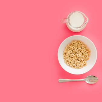 Cereales en un tazón de cerámica con leche y cuchara sobre fondo rosa