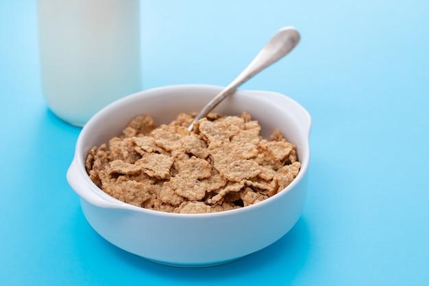 Cereales en tazón de fuente blanco sobre mesa azul