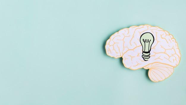Cerebro de papel con bombilla y espacio de copia