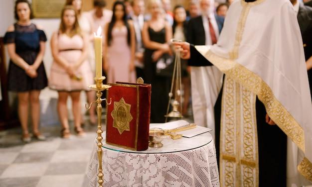 Ceremonia de boda en una iglesia ortodoxa, el sacerdote con una sotana blanca de pie en la iglesia en el