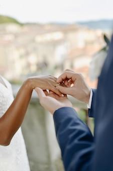Ceremonia de poner el anillo de bodas en el dedo de la novia al aire libre
