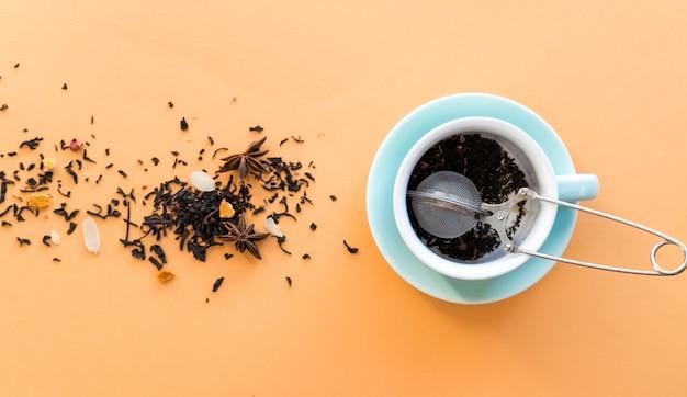 Ceremonia de preparación del té, taza verde menta, colador de té y té seco de hierbas de fruta negra sobre fondo naranja.