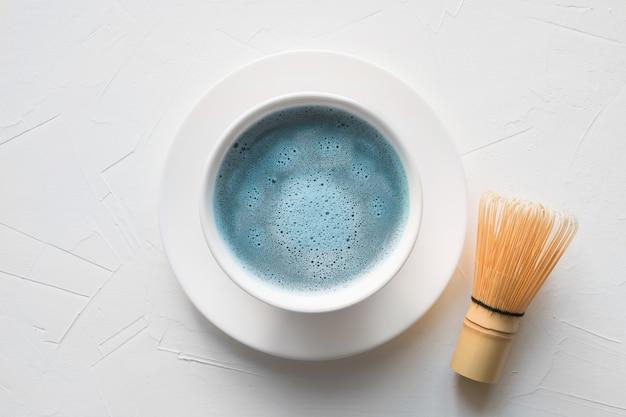 Ceremonia de té azul matcha y batidor de bambú sobre mesa de hormigón blanco vista superior