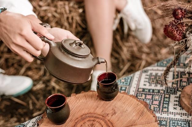 Ceremonia del té. hombre joven sentado cerca de su novia y disfrutando de su fin de semana