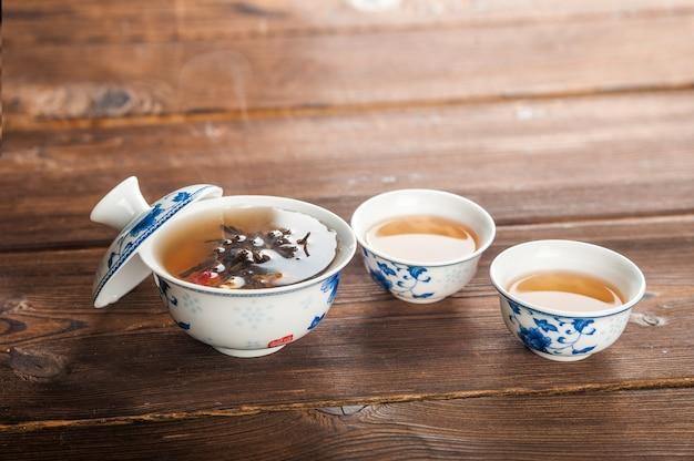 Ceremonia del té sobre un fondo oscuro de madera y espacio de la copia.