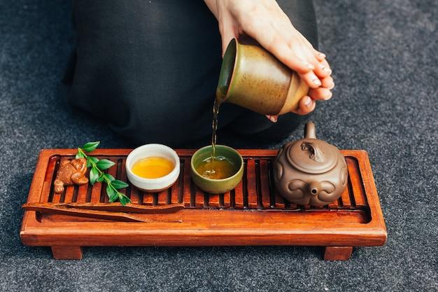 Ceremonia del té tradicional de cerca con mano de mujer