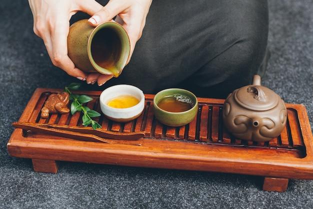 Ceremonia del té tradicional de cerca con la mano de la mujer