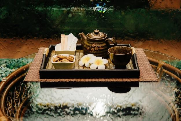 Ceremonia tradicional tailandesa famosa tetera de bronce en bandeja de mimbre con flores de loto, taza, azúcar y galletas en mesa de mimbre con superficie vidriosa con pared de cascada abstracta
