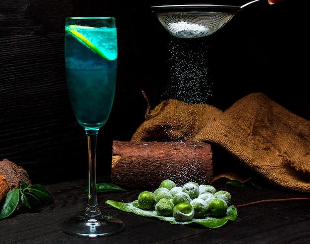 Cereza ciruela espolvoreada con sal y un vaso de bebida fría