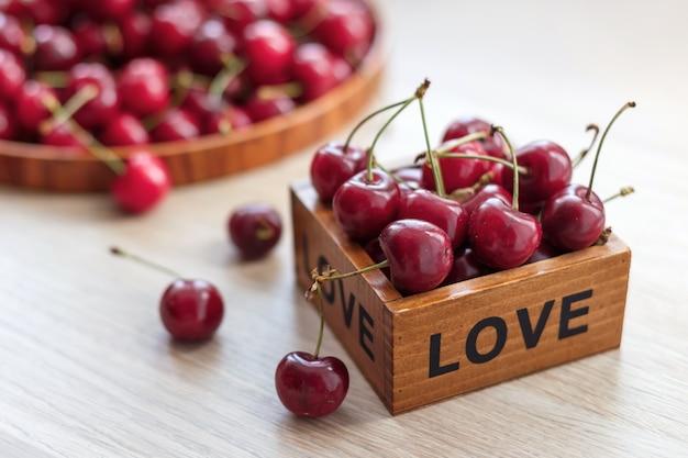 Cereza dulce fresca en una placa de madera sobre una mesa.
