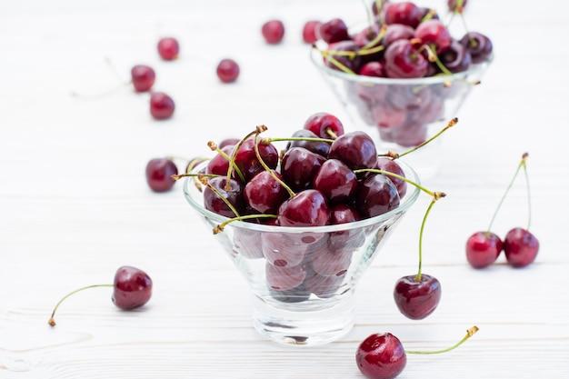 Cereza dulce madura fresca en tazones sobre una mesa de madera blanca