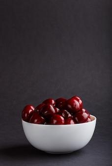 Cereza dulce roja fresca en el tazón de fuente blanco en superficie negra. vista lateral.