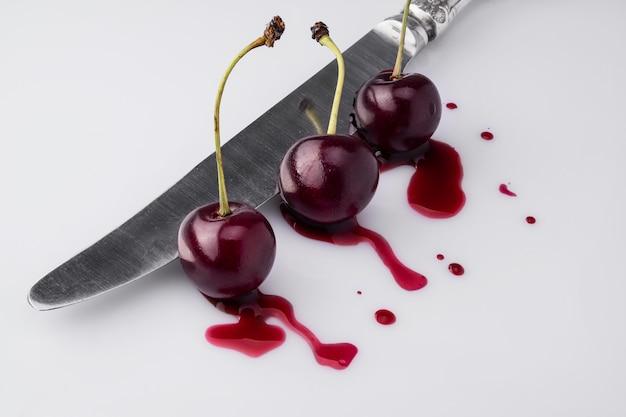 La cereza natural corta el cuchillo viejo oreginalnyy el concepto. vista desde la parte superior y lateral.