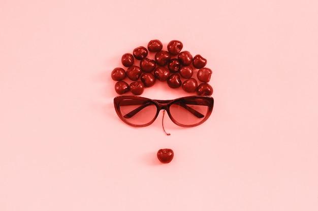 Cereza presentada en imagen de mujer con gafas de sol con labios en rosa, tono coral