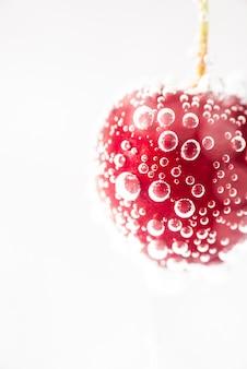 Cereza roja fresca madura del primer con agua