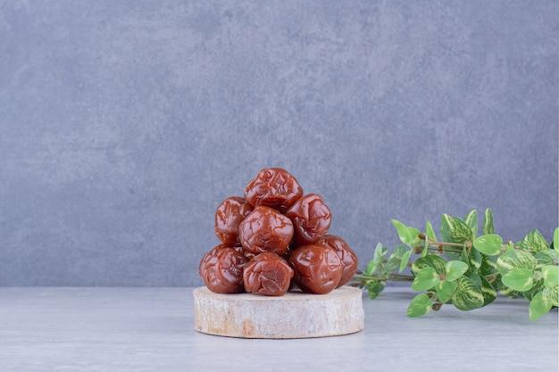 Cerezas ácidas rojas secas en una taza sobre una superficie de hormigón