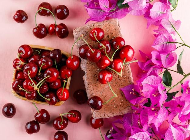 Cerezas con flores, ladrillo en una placa de madera sobre superficie rosa